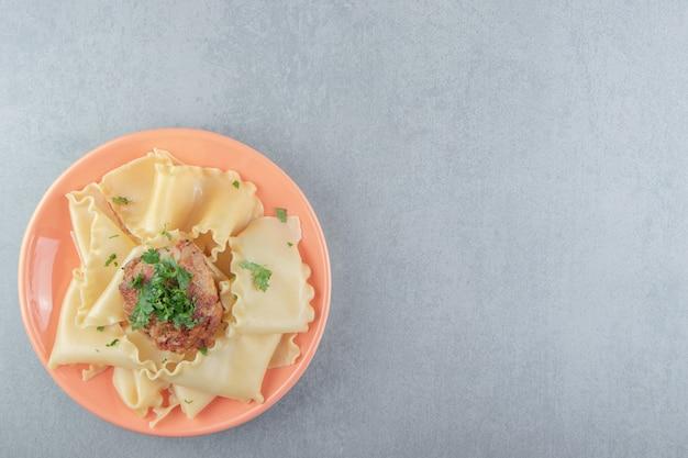 Gekookte pasta met geroosterde kip op oranje plaat.