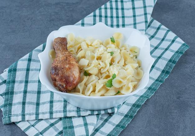 Gekookte pasta met kip drumstick in witte kom.