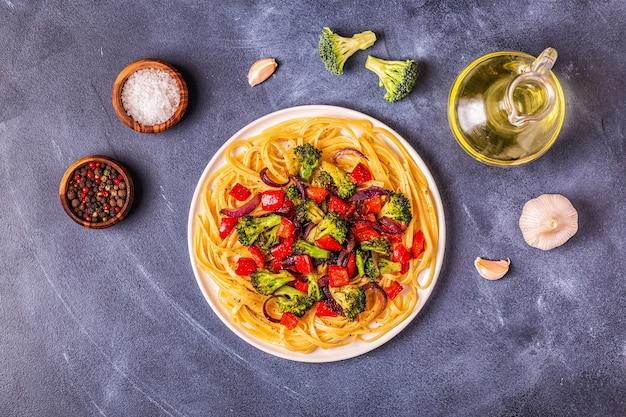 Gekookte pasta met saus van broccoli, paprika en uien