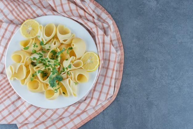 Gekookte pasta met schijfjes citroen op witte plaat.
