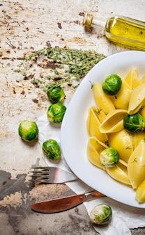 Gekookte pasta met spruitjes in een witte plaat met olijfolie. op rustieke tafel. bovenaanzicht