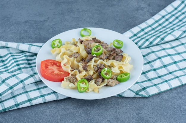 Gekookte pasta met stukjes vlees op witte plaat.