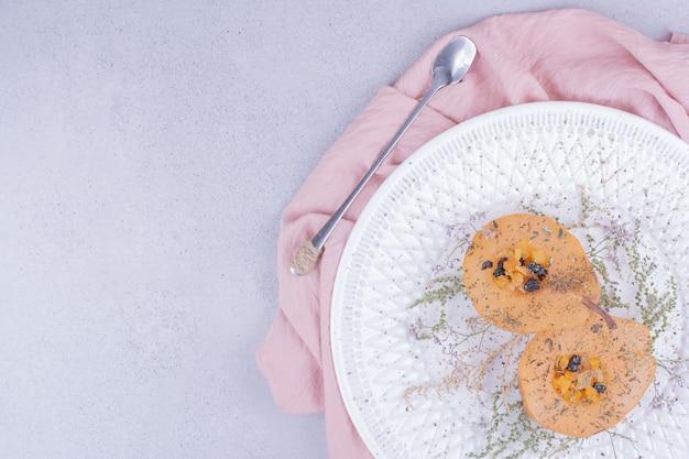 Gekookte perenplakken met kruiden en specerijen in een witte plaat.