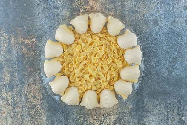 Gekookte pijp en ongekookte vlinderdaspasta's in de kom, op het marmeren oppervlak.