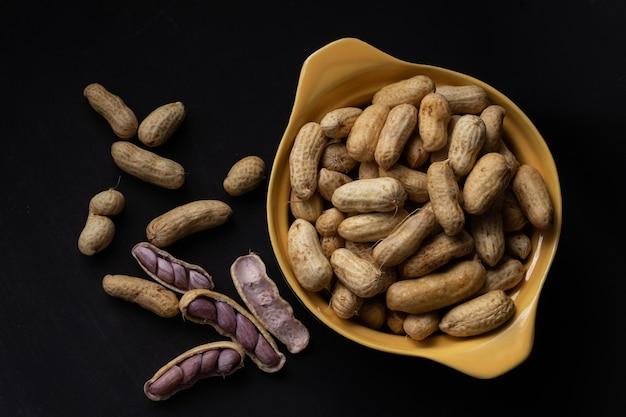 Gekookte pinda's (amendoin cozido, sergipe, nordeste, brazilië) in een zwarte en gele kom en gekookte pinda's verspreid en open buiten de kom op een zwarte achtergrond. bovenaanzicht.