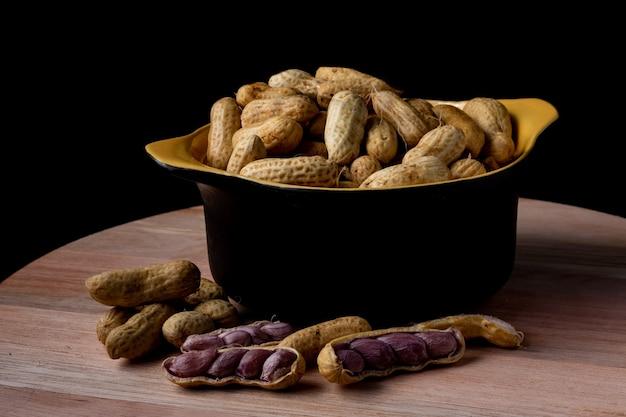Gekookte pinda's (amendoin cozido, sergipe, nordeste, brazilië) in een zwarte en gele kom en gekookte pinda's verspreid en open buiten de kom.