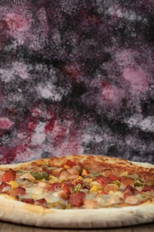 Gekookte pizza met gemengde ingrediënten met plakjes pepperoni.