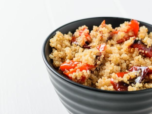 Gekookte quinoa met gebakken peper op een witte tafel. vegetarisch gerecht.