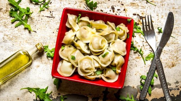 Gekookte ravioli met kruiden en olijfolie op de rustieke tafel. bovenaanzicht