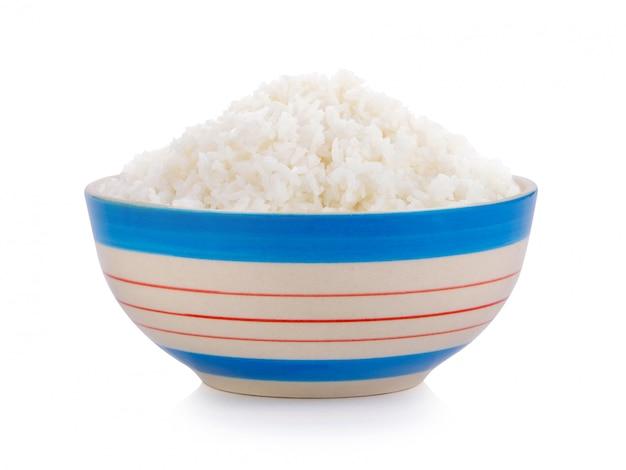 Gekookte rijst in keramische kom op witte muur