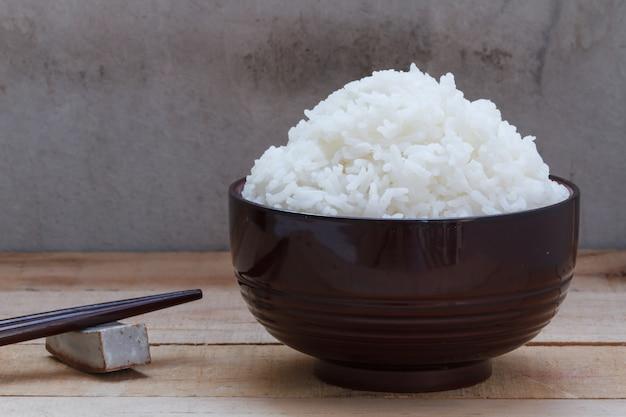 Gekookte rijst in kom op houten achtergrond