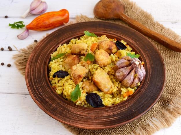 Gekookte rijst met geroosterde kip, wortelen, kruiden (traditioneel aziatisch gerecht - pilaf)