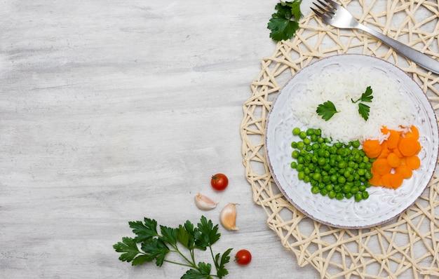 Gekookte rijst met groenten op plaat dichtbij vork