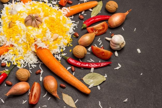 Gekookte rijst met knoflook. wortelen, uien, noten en tomaten op tafel. plat leggen