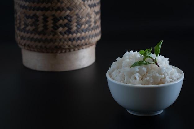 Gekookte rijst met kom op donkere zwarte ondergrond, eten en drinken concept, kopie ruimte stijl