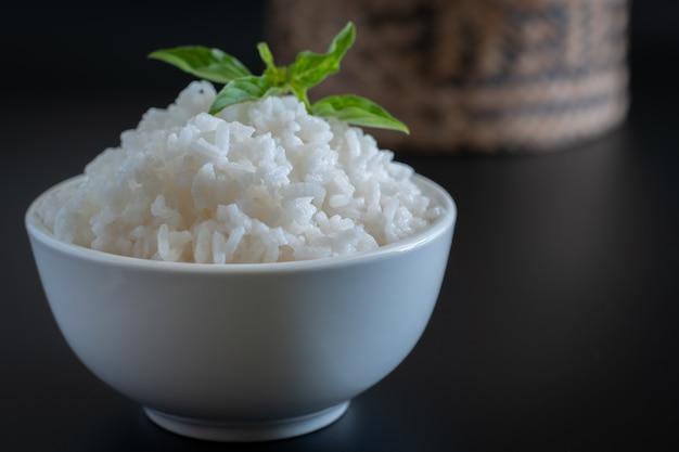 Gekookte rijst met kom op donkere zwarte ondergrond, eten en drinken concept, kopie ruimte stijl Premium Foto
