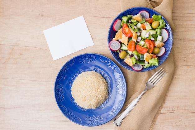 Gekookte rijst met plantaardige salade op tafel
