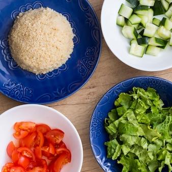 Gekookte rijst met verschillende gesneden groenten in kommen