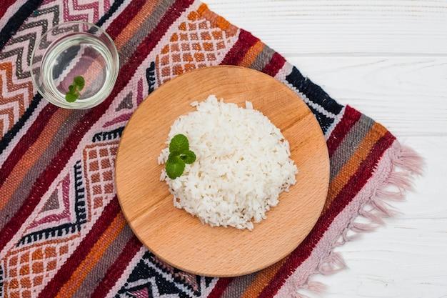 Gekookte rijst op houten bord met water