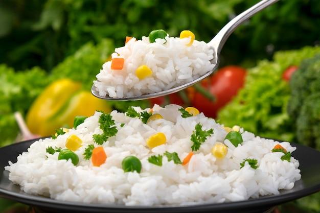 Gekookte rijsthavermoutpap op lepel, die met kruiden en groenten op zwarte plaat wordt gediend