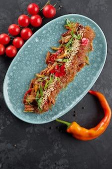 Gekookte rijstnoedels met groenten, sesamzaadjes, groene uien, kerstomaatjes en hete rode peper op een bord