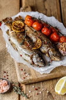 Gekookte rivierforel met kruiden en ingrediënt voor het koken op rustieke achtergrond