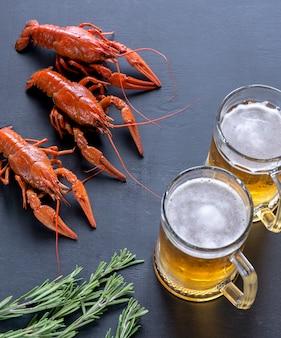 Gekookte rivierkreeft met twee mokken bier