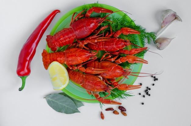 Gekookte rode rivierkreeft of rivierkreeft op een groene plaat met kruiden en rode peper