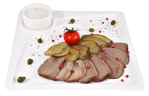 Gekookte rundvleestong met mierikswortel op een dienende plaat wit vierkant geïsoleerd