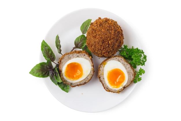 Gekookte schotse eieren op witte porseleinen plaat close-up