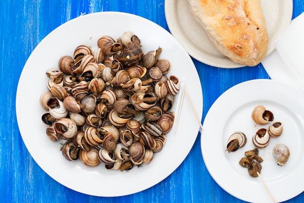 Gekookte slakken op witte plaat op blauwe houten