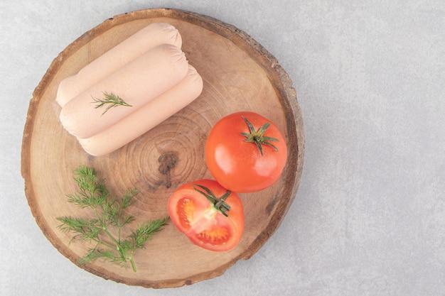 Gekookte smakelijke worstjes en tomaten op een stuk hout.