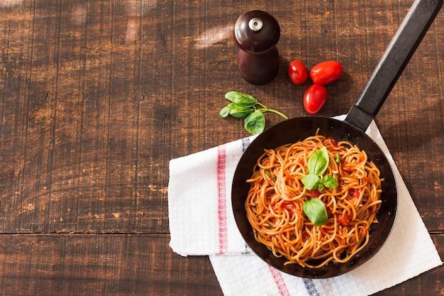 Gekookte spaghetti met basilicum en tomaten op houten lijst