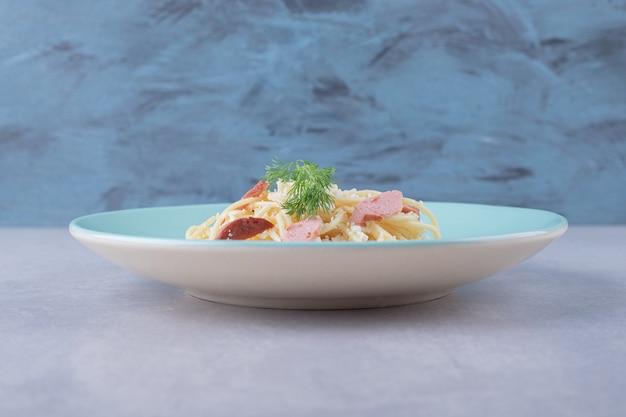 Gekookte spaghetti met gesneden worstjes op blauw bord.