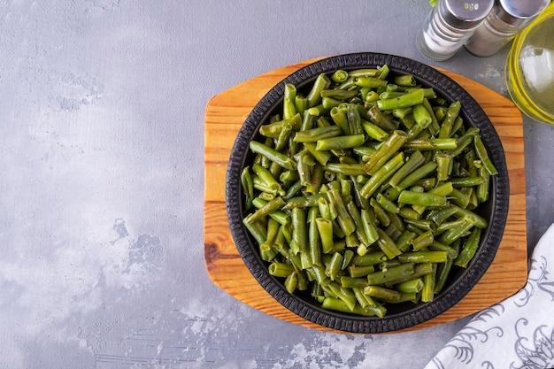 Gekookte sperziebonen met kruiden in koekenpan. tekstruimte, bovenaanzicht