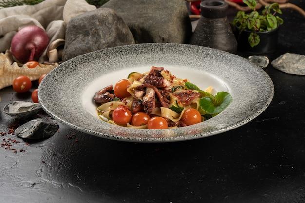 Gekookte tagliatelle pasta met octopus en cherrytomaatjes