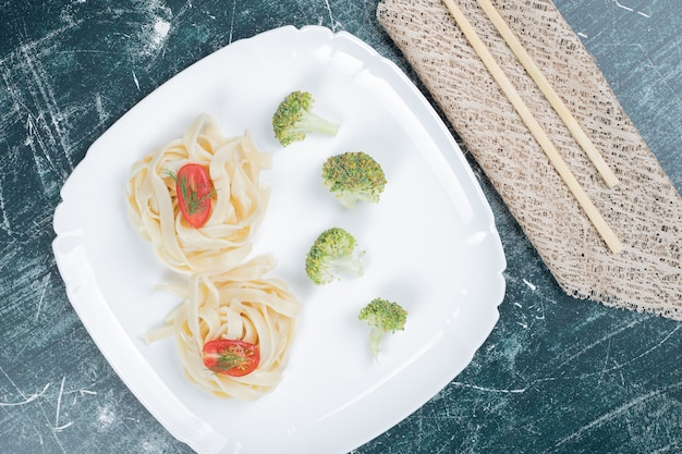 Gekookte tagliatelle pasta op een witte plaat met plakjes broccoli en tomaat. hoge kwaliteit foto