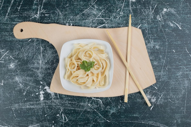 Gekookte tagliatelle pasta op witte plaat met stokjes.