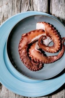 Gekookte tentakels van octopus op blauwe keramische plaat over grijs houten oppervlak. bovenaanzicht, plat gelegd