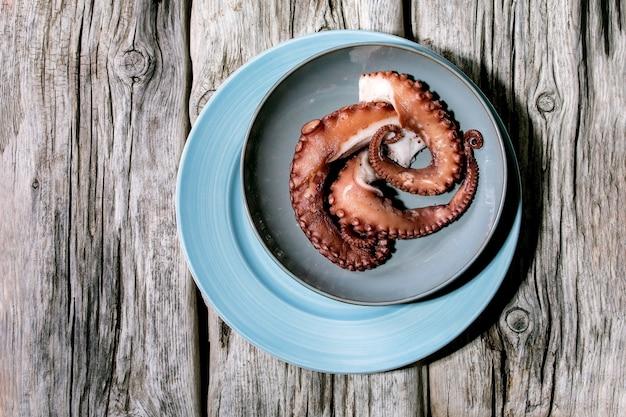 Gekookte tentakels van octopus op blauwe keramische plaat over oud grijs houten oppervlak. bovenaanzicht, plat gelegd. ruimte kopiëren