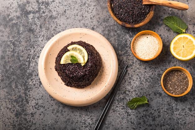 Gekookte thaise zwarte jasmijnrijst met chiazaad, citroen, sesam op betongrijze achtergrond.
