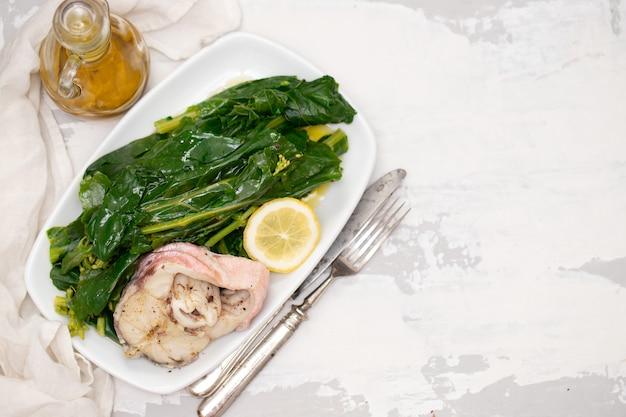 Gekookte vis met citroen en groenten op witte schotel