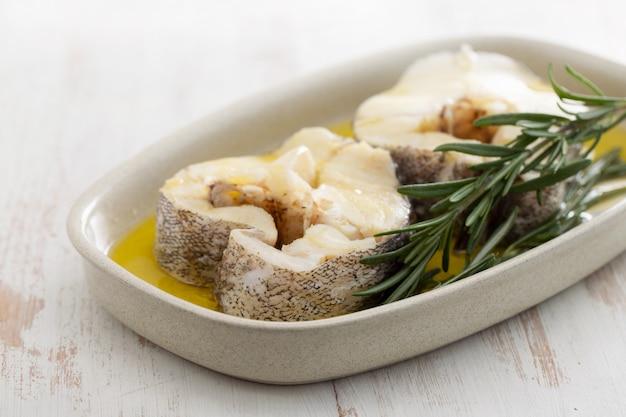 Gekookte vis met olijfolie en rozemarijn in schotel