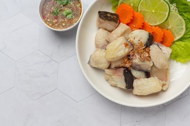Gekookte vis met pikante dipsaus en groente