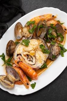 Gekookte vis met zeevruchten op schotel