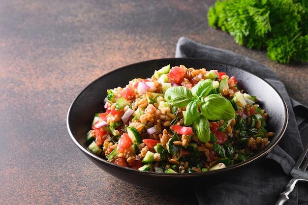 Gekookte volkoren speltsalade met seizoensgroenten in kom op donker. detailopname.