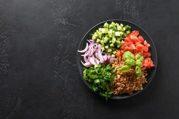 Gekookte volkoren speltsalade met seizoensgroenten in kom op zwarte achtergrond.