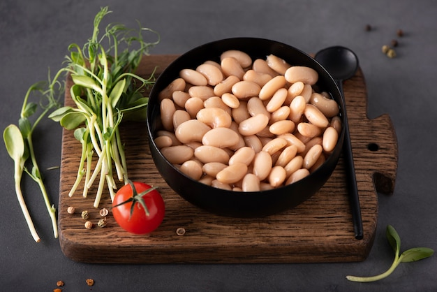 Gekookte witte bonen met kruiden en specerijen in een zwarte kom, close-up