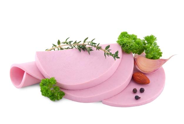 Gekookte worst die met salade en knoflook wordt gesneden die op wit wordt geïsoleerd