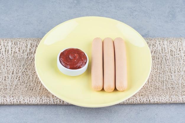 Gekookte worst en ketchup op gele plaat.